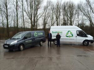 A young Sam Kingdon shows off his first 2 vans beside his first ever employee