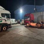 Liveried commercial vehicles in a flood-lit yard at night