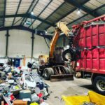 Case Poclain 360 Excavator loading a bulk trailer with small mixed WEEE indoors