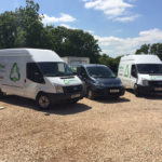 Three small liveried vans in a rural yard