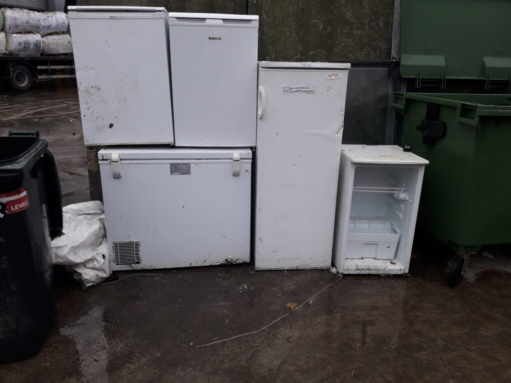 Various domestic fridges and freezers on the ground